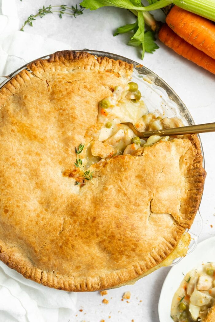 chicken pot pie in pie dish with a slice removed