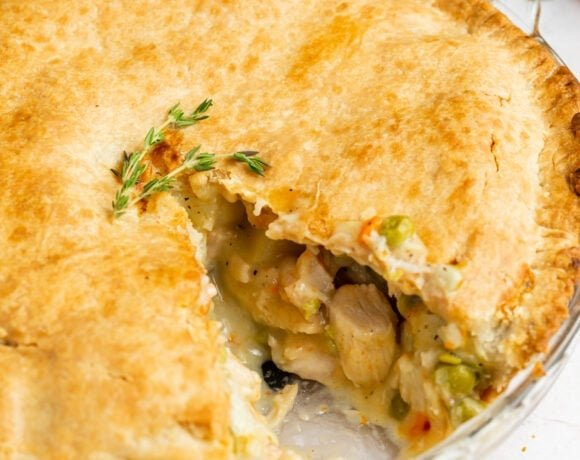 chicken pot pie with a slice removed and carrots on the side