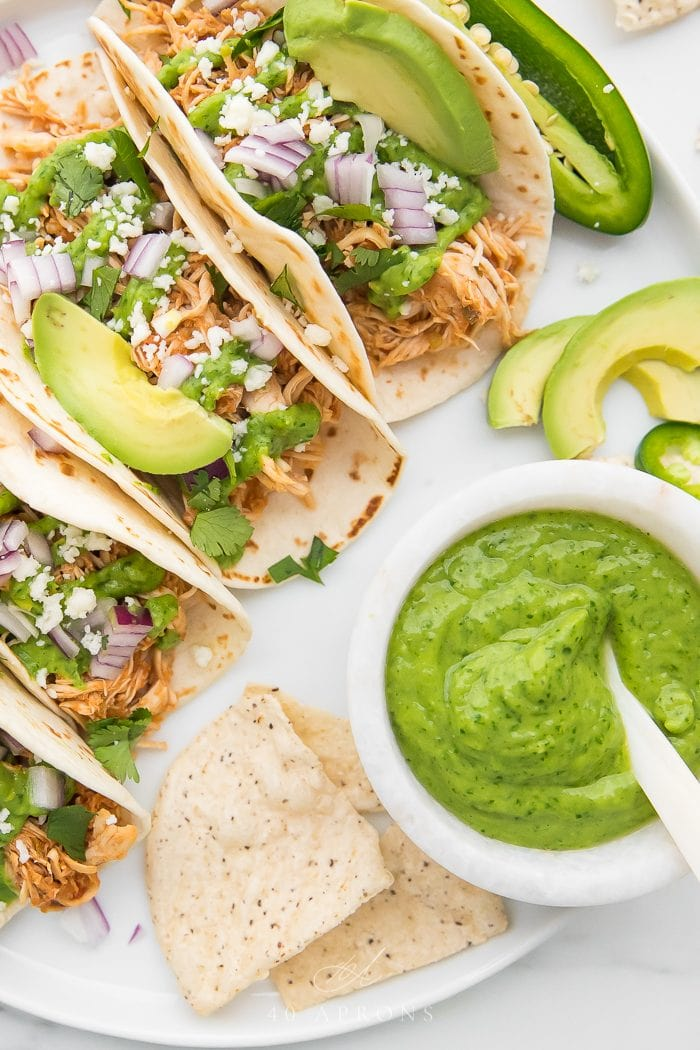 Crockpot chicken tacos with a bowl of avocado cilantro sauce