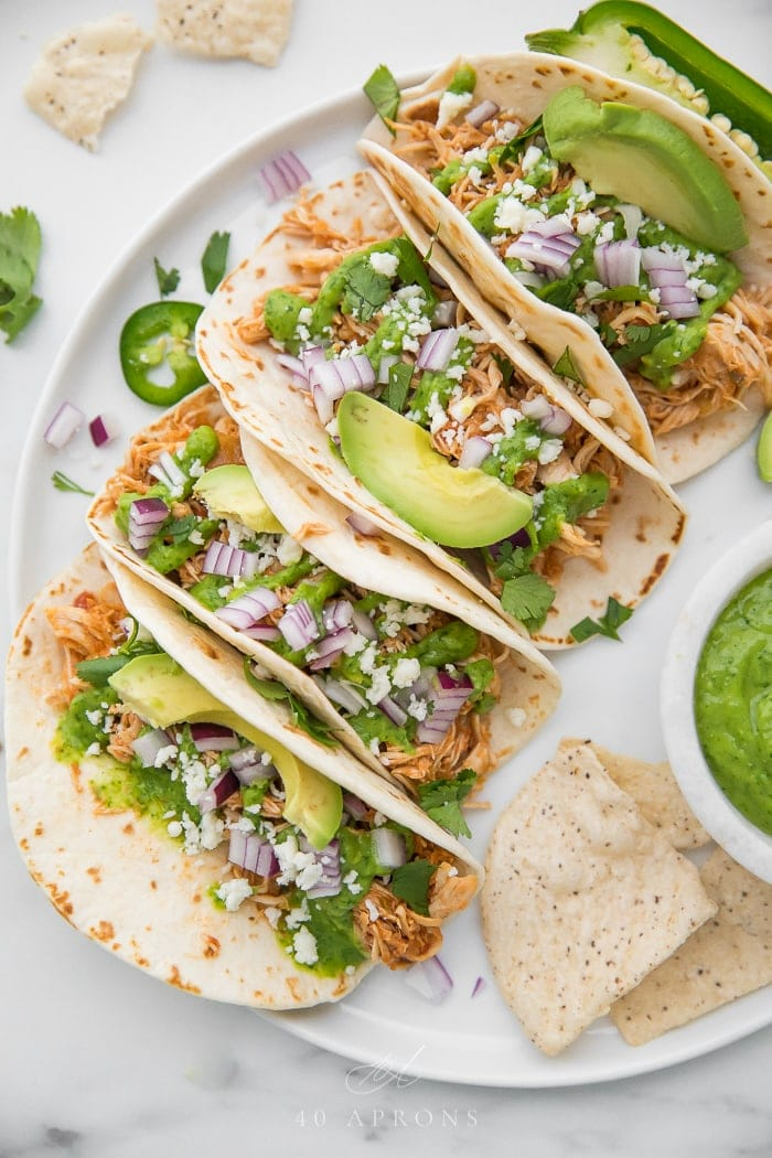 Crockpot chicken tacos on a white plate with avocado cilantro sauce and queso fresco