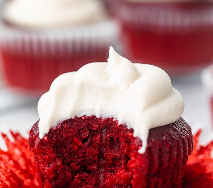 A vegan red velvet cupcake with a bite missing