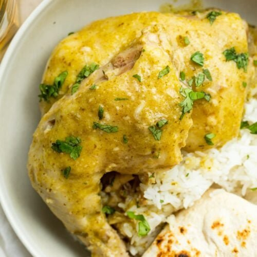 overhead image of green mole chicken on a plate with rice and a tortilla
