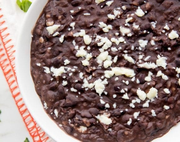 Bowl of refried black beans with queso fresco