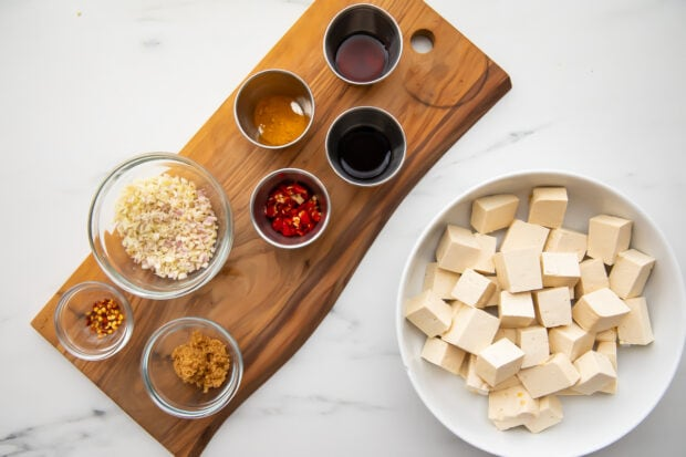 All ingredients for lemongrass tofu, with tofu in a large bowl