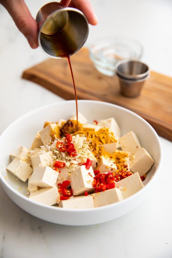 Lemongrass tofu marinade poured over tofu in a large bowl