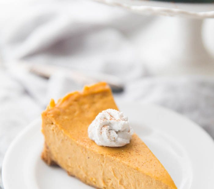Vegan pumpkin cheesecake with whipped coconut cream on a plate
