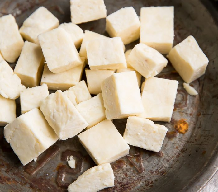 Cubes of paneer Indian cheese in a metal dish