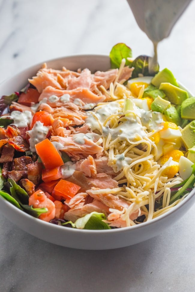 An absolute explosion of flavor, this smoked salmon cobb salad is layered with crisp bacon, creamy smoked gouda, cubed avocado, and tender boiled eggs.