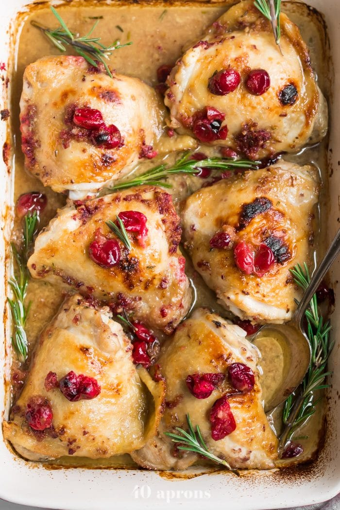 Paleo cranberry rosemary one pan chicken thighs in a baking dish topped with cranberries and fresh rosemary