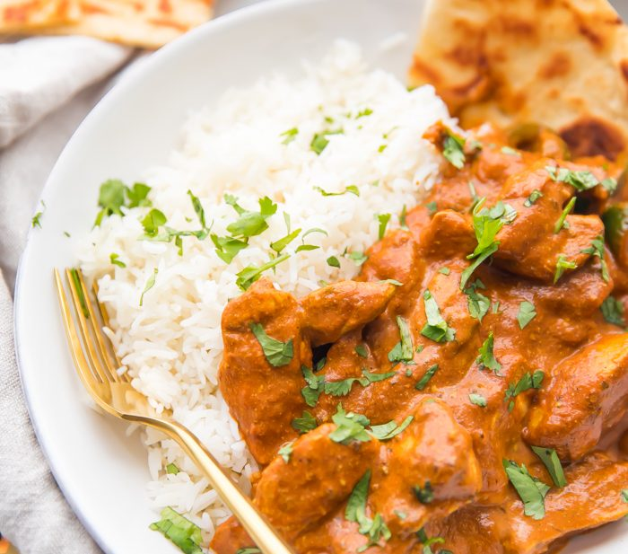 Best chicken tikka masala recipe over rice with naan in a white bowl with skillet in the background