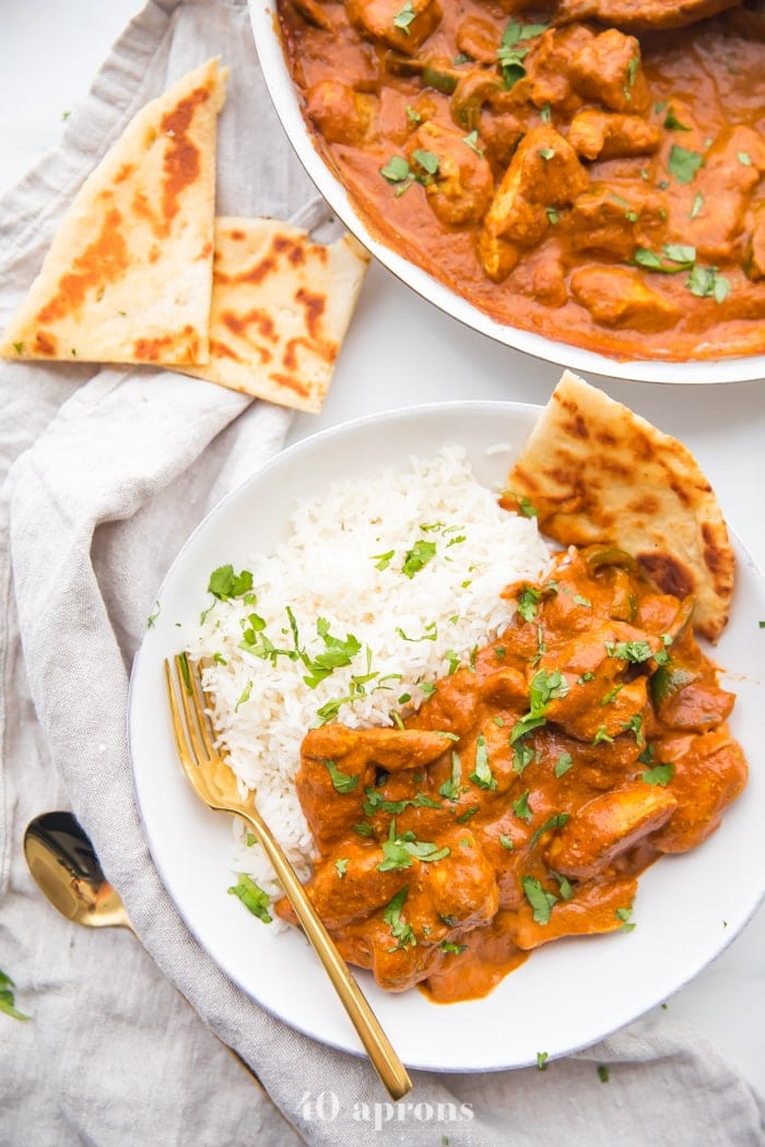 Overhead shot of the best chicken tikka masala recipe over rice with naan in a white bowl with skillet to the side