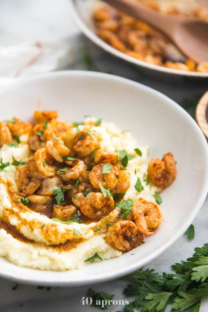 Whole30 healthy shrimp and grits in a bowl with skillet in background
