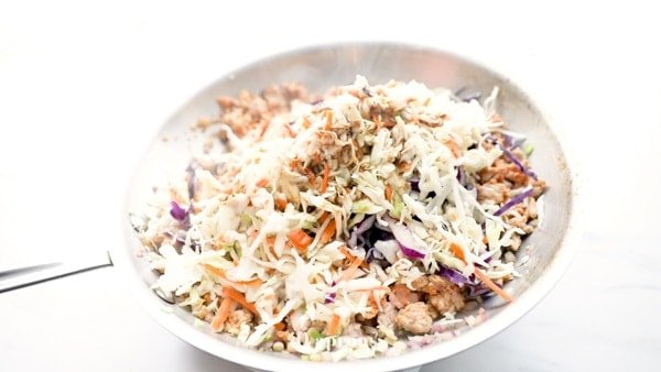 shredded cabbage or coleslaw, coconut aminos, rice wine vinegar, white pepper, and salt frying in a pan to make crack slaw
