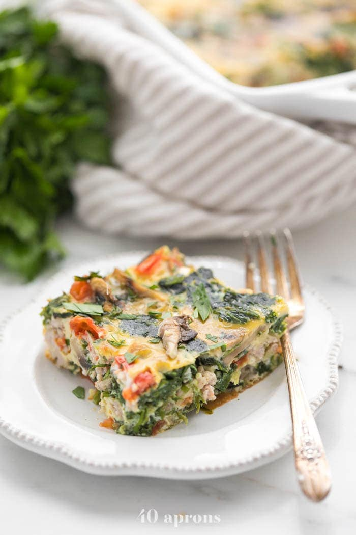 Slice of Whole30 breakfast casserole with sausage on a plate with casserole in background