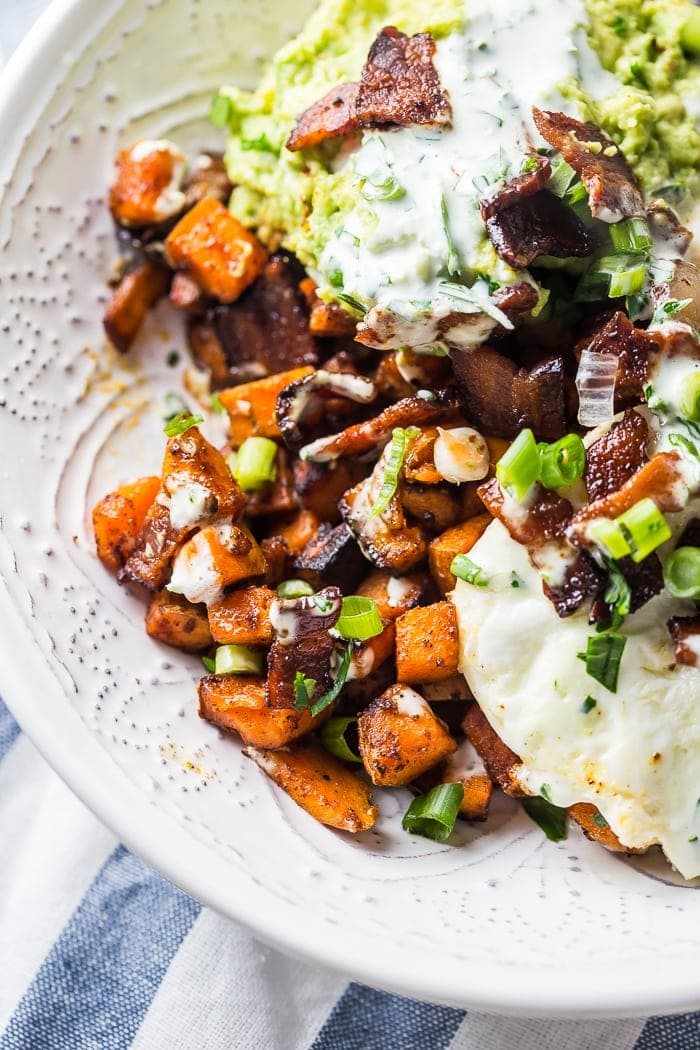These Whole30 loaded sweet potato fries will surprise you with just how delicious they are. Filling enough for a Whole30 dinner, this recipe is also an excellent Whole30 side dish. With bacon, fried eggs, guacamole, green onions, and garlicky ranch dressing, you'll never feel like you're depriving yourself on a Whole30 with this recipe in your arsenal.
