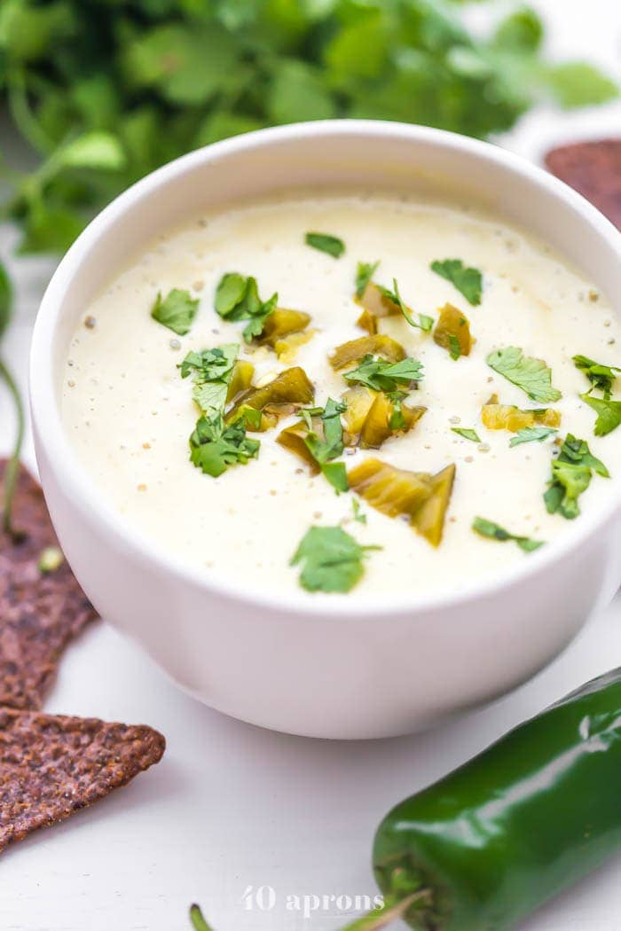 A bowl of the best vegan queso recipe with cilantro and chips around