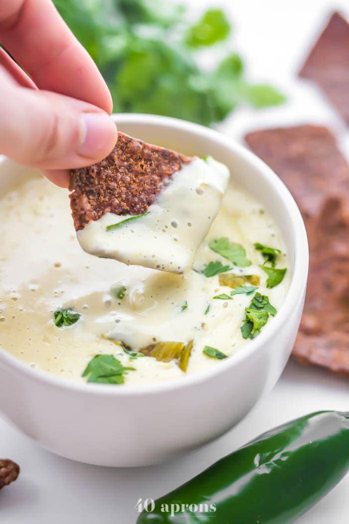 A bowl of the best vegan queso recipe with cilantro and a chip dipping