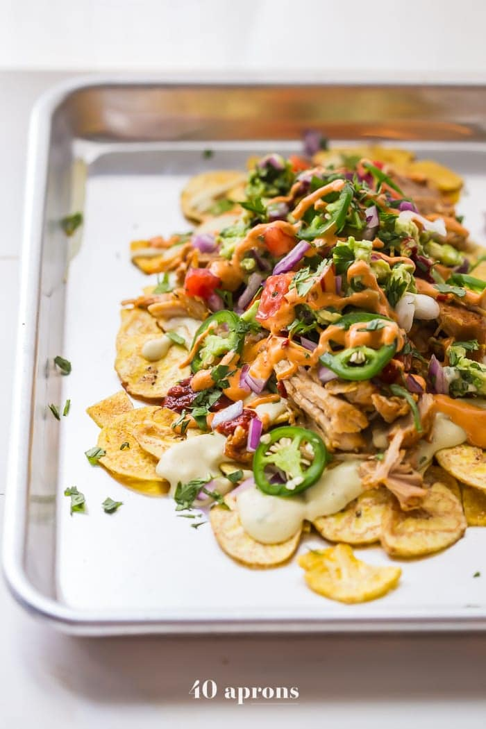 These paleo nachos are epic, aka the best paleo nachos ever. What makes paleo nachos epic, you ask? Well, what do you think of plantain chips topped with tender carnitas, the best paleo queso blanco, guacamole, pico de gallo, smoky guajillo salsa, and creamy chipotle sauce? If those doesn't sound like the best paleo nachos to you, I just don't even know who you are anymore.