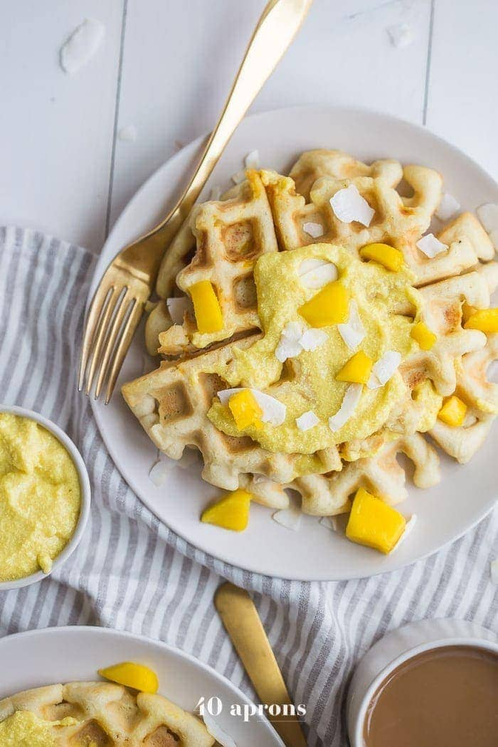 These paleo coconut waffles with sweet mango cream are tender and light, sweet and flavorful. Topped with a sweet mango cream made from healthy, real ingredients, this dish will become your favorite paleo breakfast recipe! And if you're asking me, this is the best paleo waffle recipe - the texture is light and fluffy, but you'll feel energized instead of sluggish after a stack. Perfect for spring and summer!