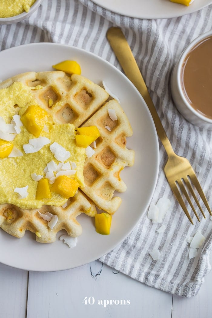 These are the best paleo waffles, topped with sweet mango cream. They're tender and light, sweet and flavorful. Topped with a sweet mango cream made from healthy, real ingredients, this dish will become your favorite paleo breakfast recipe! And if you're asking me, this is the best paleo waffle recipe - the texture is light and fluffy, but you'll feel energized instead of sluggish after a stack. Perfect for spring and summer!