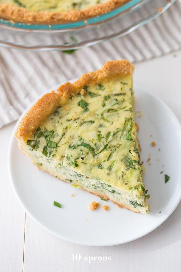 This paleo quiche with crab and spinach is a fantastic paleo Mother's Day brunch recipe, but it's versatile and quick enough to become a favorite paleo dinner or paleo brunch dish in your rotation. With an almond flour crust, this paleo quiche is so much like a cheesy, gluteny quiche!