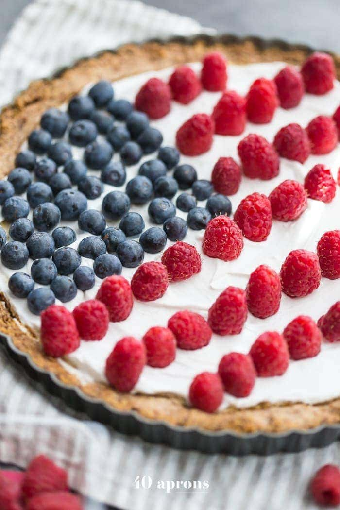 This paleo flag fruit tart is Fourth of July dessert perfection. With a coconut oil shortbread crust, rich almond fangiapane filling, and topped with cool coconut cream and fresh fruit, you've got your paleo Fourth of July dessert covered. Why make a paleo 4th of July cake when you can make a tart delicious enough to beat all other paleo 4th of July desserts?! U-S-A! U-S-A!