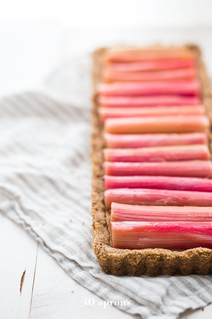 This paleo rhubarb tart is layered with a buttery shortbread crust, rich almond frangiapane filling, and finished with a perfectly sweet, tart rhubarb topping. This paleo rhubarb dessert is absolutely stunning and positively delicious, making it perfect for summer entertaining. This paleo rhubarb tart is a must-try!