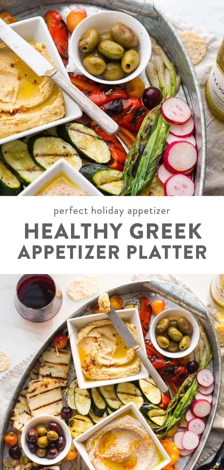 Healthy greek appetizers on a platter with wine on a table.