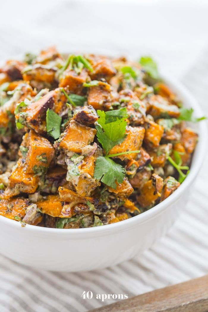This herb roasted Whole30 sweet potato salad is perfection: crispy sweet potatoes coated in a rich and creamy herb mixture, topped with crunchy red onions. Perfect at a Whole30 picnic, alongside a Whole30 dinner recipe, or as a lunch side dish all week long, you'll love how flavorful this roasted Whole30 sweet potato salad is. Elegant enough for company but easy enough for a weeknight! Vegan option to make this an herb roasted vegan sweet potato salad, too.