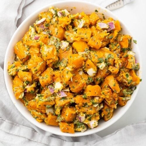 Sweet potato salad in a white bowl on a marble countertop
