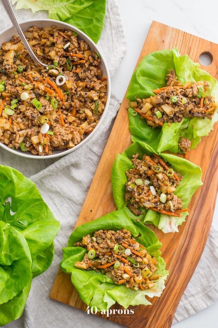 Healthy PF Changs lettuce wraps recipe on a board with a bowl of filling to the side