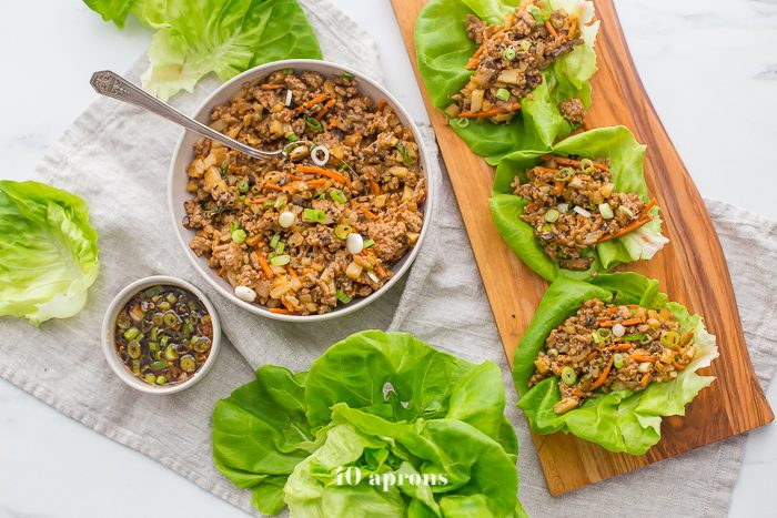 Healthy PF Changs lettuce wraps recipe on a board with a bowl of filling to the side and lettuce leaves