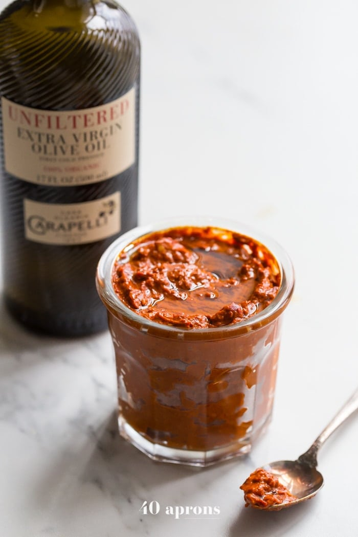 homemade harissa in a small glass dish with a bottle of carapelli olive oil in the background