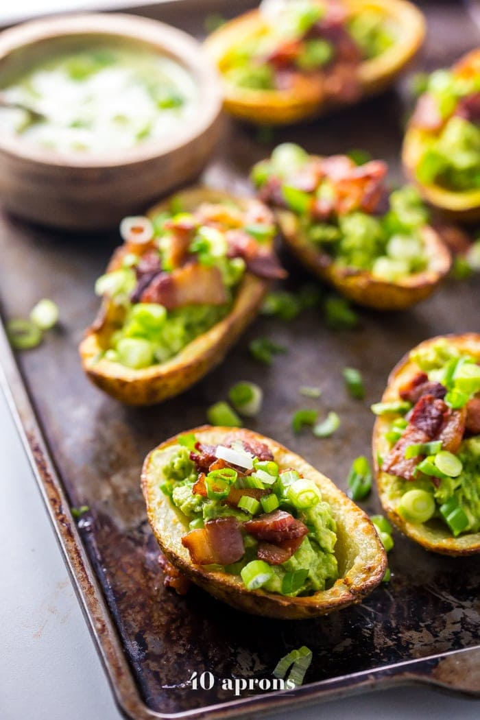 These paleo potato skins are seriously perfect paleo tailgate food. These paleo potato skins are super crispy and easy to make, loaded with a quick guacamole, crispy bacon, green onions, and ranch dressing. Yep, these Whole30 potato skins are perfect alongside buffalo wings and beer, and they'll quickly become your favorite paleo tailgate food.