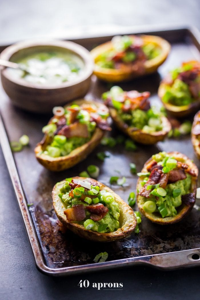 Paleo potato skins on a cookie sheet and topped with guacamole and bacon
