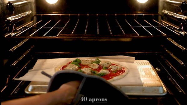Slide pizza on parchment onto preheated overturned baking sheet