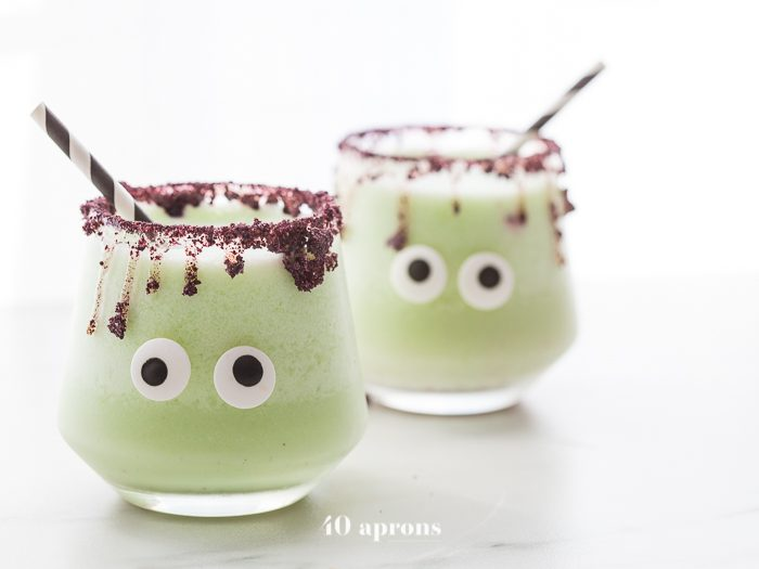 Monsteritas green Halloween cocktails with purple dripping rim and candy monster eyes in glasses with a black and white straw