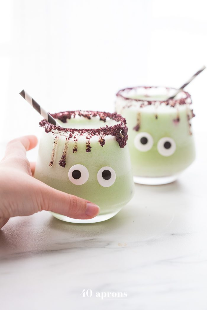 Monsteritas green Halloween cocktails with purple dripping rim and candy monster eyes in glasses