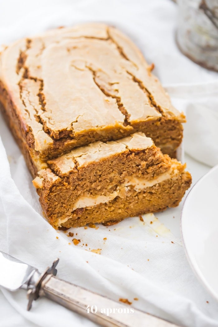 Paleo pumpkin bread with cream cheese swirl sliced with a bite out of one piece