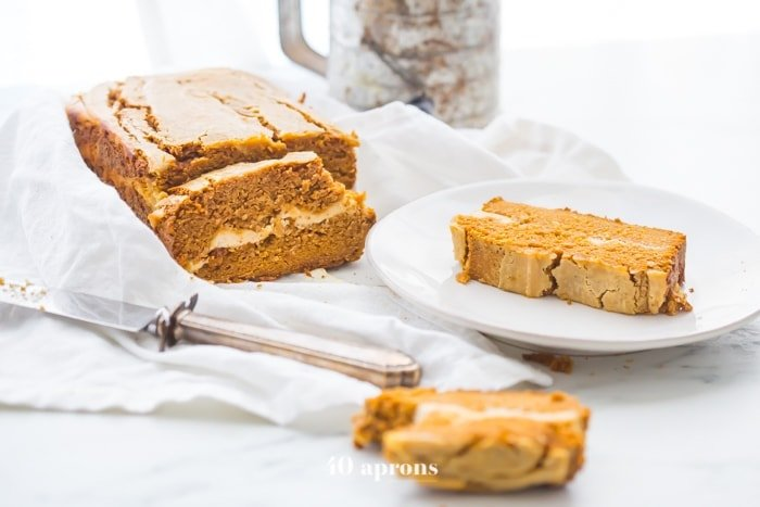 Paleo pumpkin bread with cream cheese swirl sliced with one piece on a plate