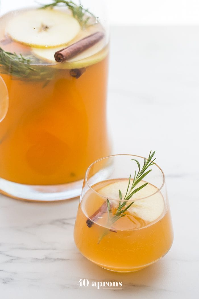 Glass and jug of cinnamon apple cider mimosa recipe with rosemary, slice of apple, cinnamon stick