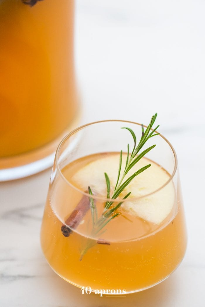 Glass of cinnamon apple cider mimosa with sprig of rosemary, cinnamon stick, and slice of apple