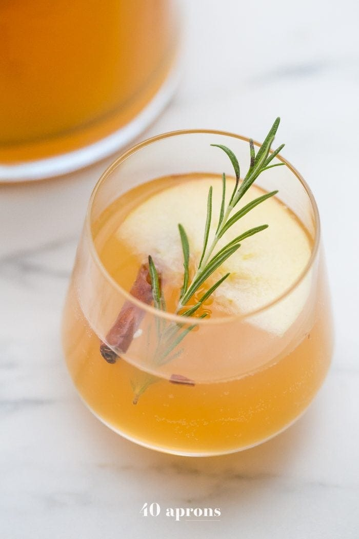 Cinnamon apple cider mimosa in a glass with a slice of apple, cinnamon stick, and sprig of rosemary