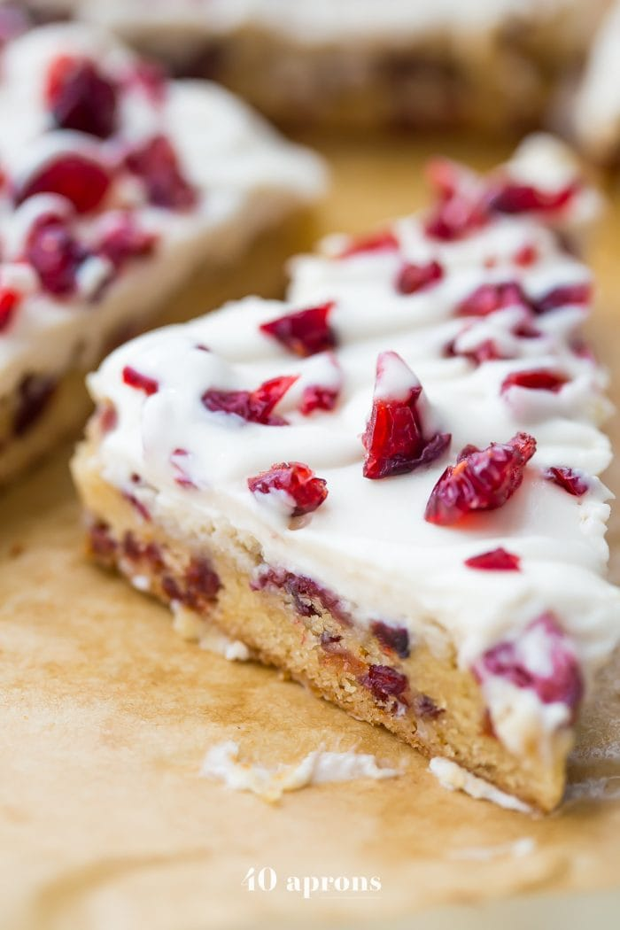 "These paleo cranberry bliss bars are just that: bliss! These vegan cranberry bliss bars are a grain-, gluten-, and dairy-free paleo Starbucks copycat recipe that's perfect for the holidays. Blondies, layered with ""cream cheese"" frosting, topped with dried cranberries, these paleo cranberry bliss bars are so delicious. You'll love these vegan cranberry bliss bars because they're a holiday treat that are totally guilt-free!"