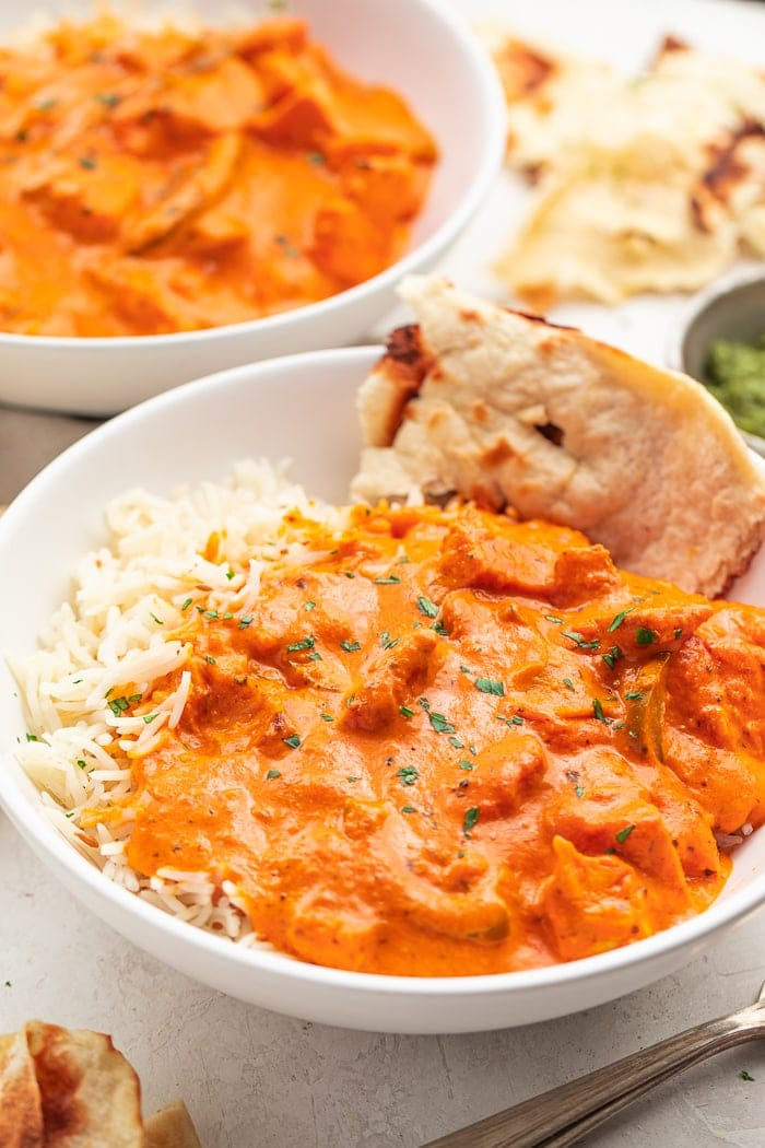 Two bowls of chicken tikka masala with rice and naan
