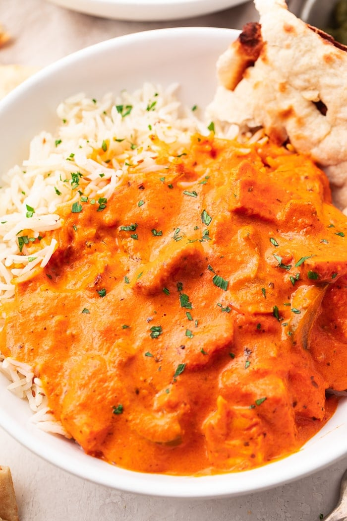 A bowl of chicken tikka masala over basmati rice with a slice of naan