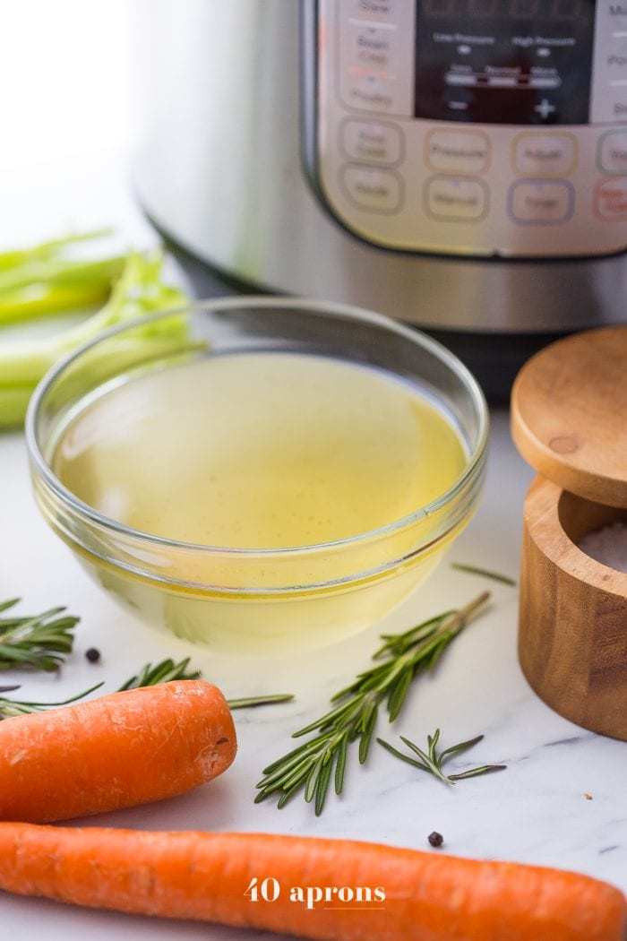 Instant Pot bone broth in a bowl with Instant Pot, carrots, herbs, and salt