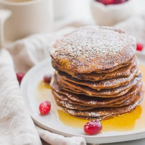 Stack of paleo gingerbread pancakes on a white plate with maple syrup around the bottom and fresh cranberries as garnish