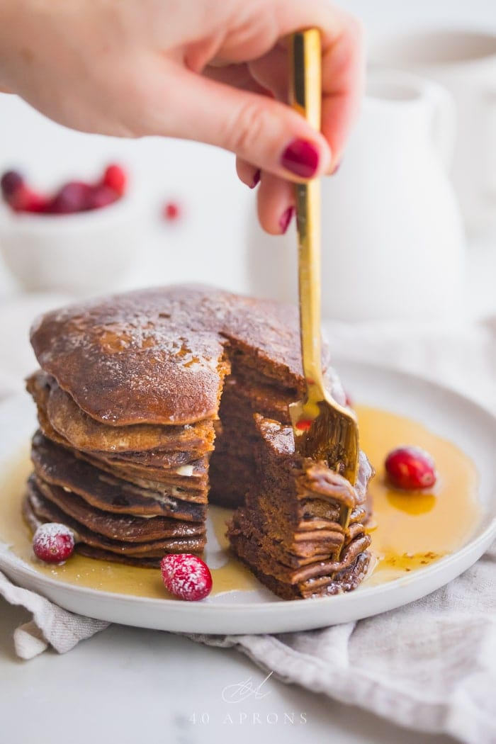 Stack of paleo gingerbread pancakes on a white plate with maple syrup around the bottom and a big bite cut out with a gold fork held between fingers in the piece and fresh cranberries as garnish