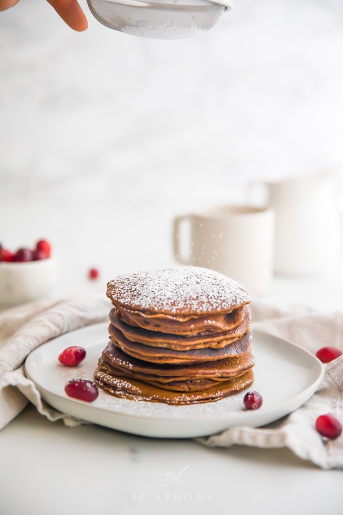 Stack of paleo gingerbread pancakes on a white plate with powdered sugar on top and fresh cranberries as garnish